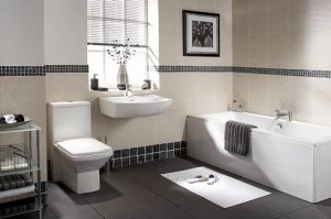 High contrast bathroom with dark tiles and light bathmat, dark towel on white tub.