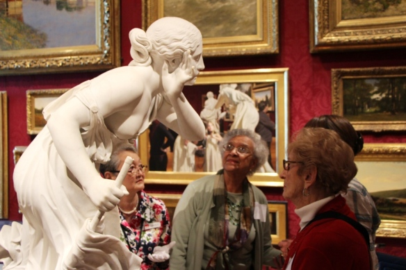 Members of the Sharon-Stouton Low Vision Support Group attend a Feeling for Form tour at the Museum of Fine Arts. One support group member (left) is wearing gloves to touch select sculptures.