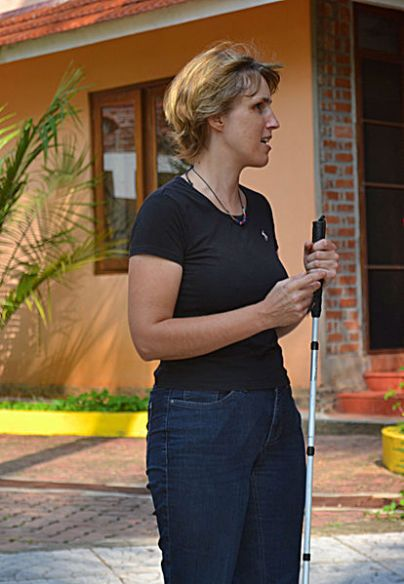 Sabriye Tenberken, a co-founder of Braille Without Borders, appears at the campus of kanthari international. She is wearing a short-sleeved black shirt and has a white cane. Photo Courtesy of Wiki Commons.
