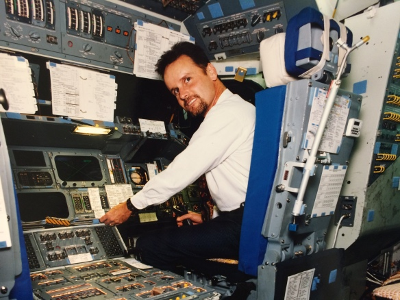 A younger Tracy sitting in a space shuttle cockpit, operating the controls.