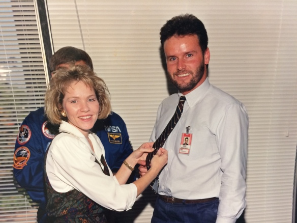"An older picture of Tracy's wife pinning the Astronaut Office's ""Silver Snoopy"" award to her husband's tie."