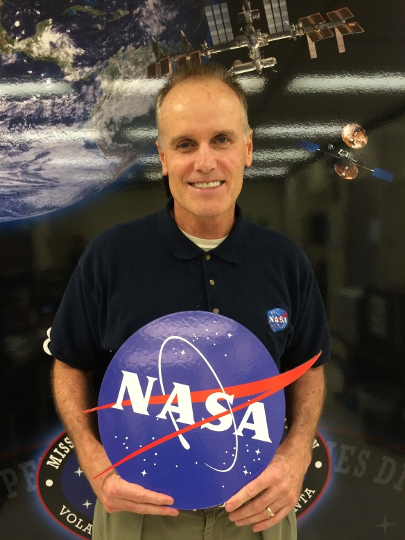"Benjamin ""Tracy"" Minish holding a NASA sign in front of an artificial space backdrop."