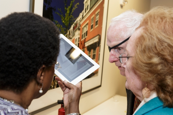 An OT demonstrates the TapTapSee app for a man and a woman, using an iPad to identify a fire extinguisher.