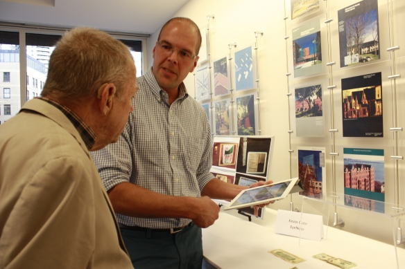 An OT demonstrates the EyeNote app on an iPad for a man.