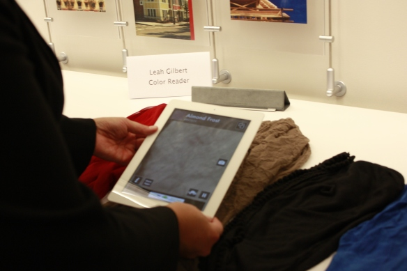 A woman uses the ColorID app on an iPad to identify the color of a sweater on a table.