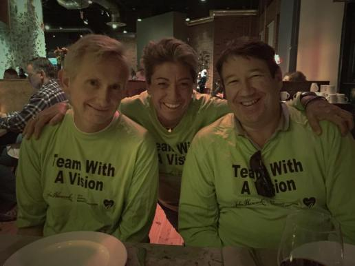 David McCord and Stephen Hendrickson with Team With A Vision runner Diane Berberian, all wearing grean Team With A Vision shirts