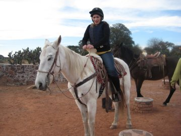 Sinead Kane riding a white horse in Mexico