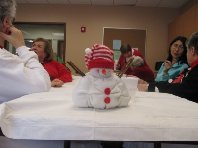 A stuffed snowman wearing a winter hat sits on a table at the Natick support group meeting