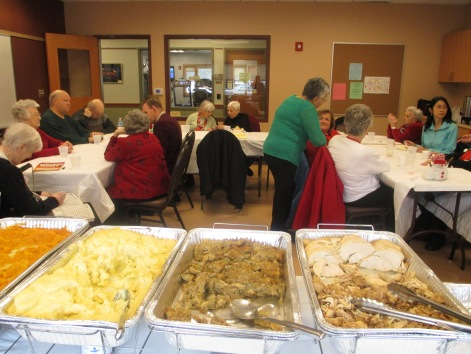 Foreground: trays of food, such as turkey and mashed potatoes, Background: the Natick support group members sit around tables and chat