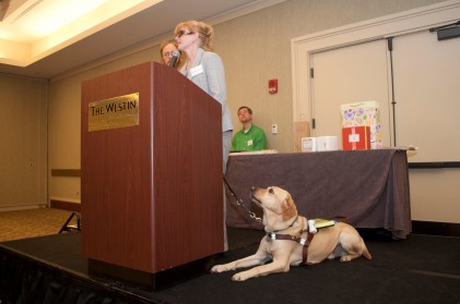 Jen Buchanan speaking at a podium at a MABVI Volunteer Appreciation Brunch, with her guide dog Keating on the ground looking up at her