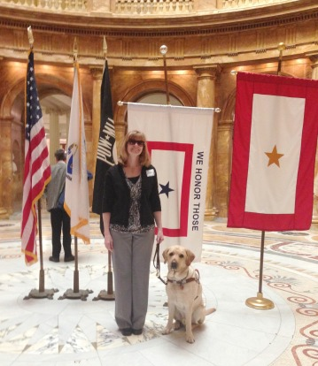 Jen and Keating in front of flags at the State House for B.L.I.N.D. (Blind Legislative Informational Networking Day)