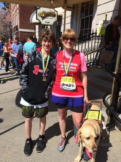 Jen Buchanan, her son Ryan, and her guide dog Keating pose outside Cheers in Boston after both Jen and Ryan ran in the B.A.A. 5K 2015