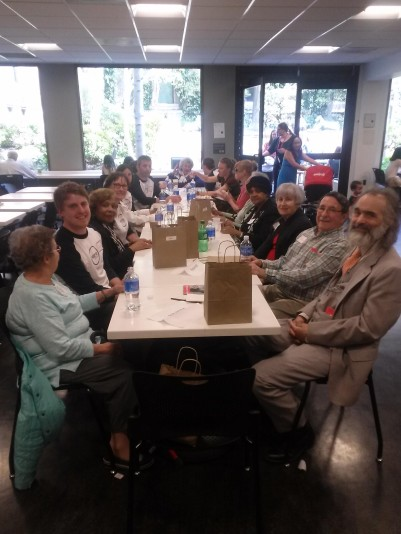 The Liberty Mutual volunteers, low vision support group members, and MABVI staff sit at a long table