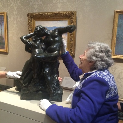 A low vision support group member touches a sculpture at the MFA Feeling for Form program