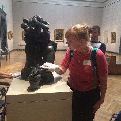 MABVI low vision support group members and staff touch a sculpture at the MFA while a Liberty Mutual volunteer looks on