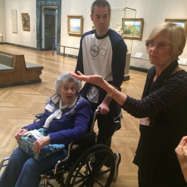 A Liberty Mutual volunteers pushes a low vision support group member in a wheelchair as the MFA guide speaks to the group