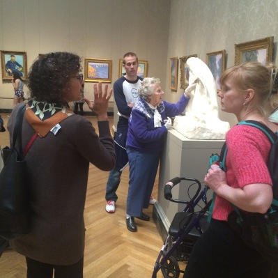 An MFA guide speaks while a support group members touches a sculpture and a Liberty Mutual volunteer looks on