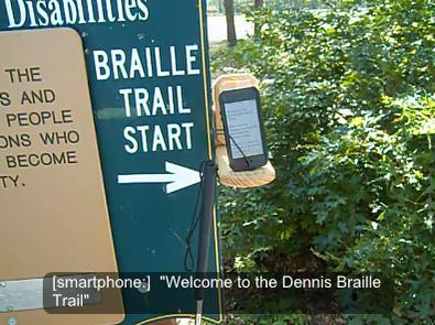 "A photo of a smartphone in the LaunchGuide location, with a sign reading ""BRAILLE TRAIL START"" pointing to the phone in the wire guides and a caption on the photo that reads ""[smartphone:] Welcome to the Dennis Braille Trail"""