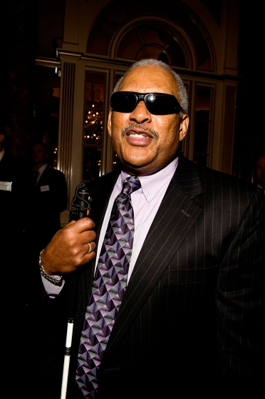 Dean posing for a photo, wearing a suit and sunglasses and holding a cane