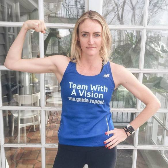 Heather B. Armstrong posing in a blue Team With A Vision shirt, flexing her right arm