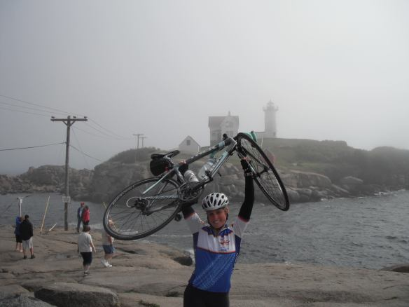 Megan in biking gear holding her bicycle above her head by the ocean with a lighthouse in the background