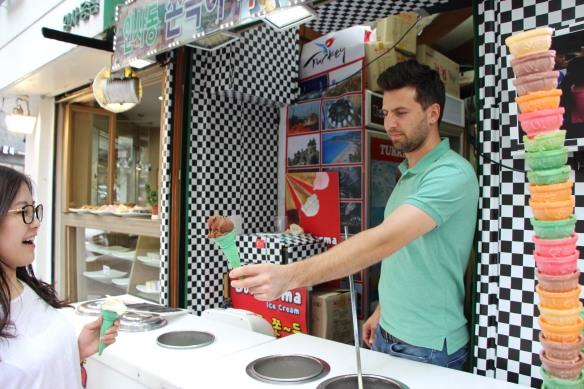 An ice cream vendor handing a customer a cone